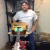 Fret boss wearing work goggles, standing beside a guitar undergoing major surgery.