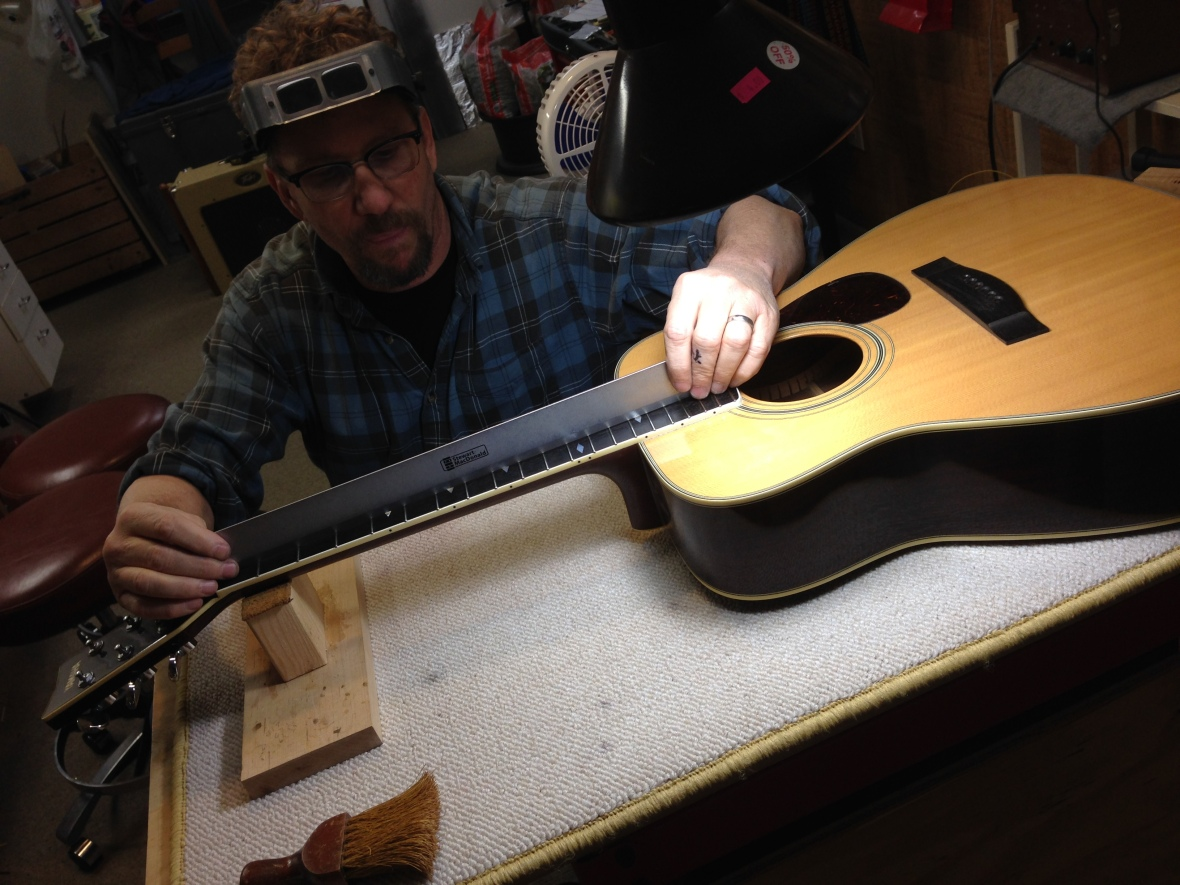 Using a ruler to check the level of frets on an acoustic guitar