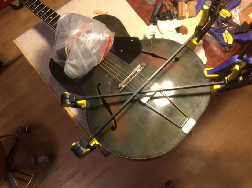 several clamps holding the edges of the guitar